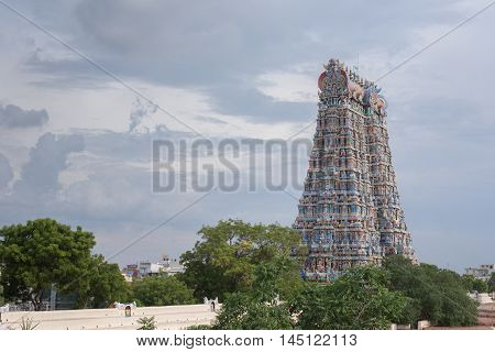 Madurai India - October 19 2013: The East Gopuram of the Meenakshi temple is shot from the North. Cloudy skies and green trees in photo.