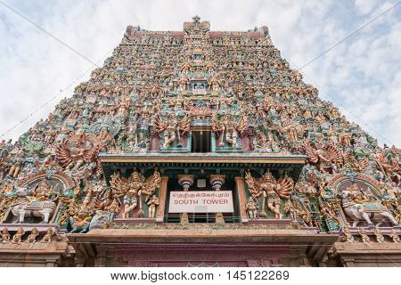 Madurai India - October 19 2013: Vertical shot along the facade of the South Gopuram. End in the sky. Abundance of statues and pallet of pastel colors.