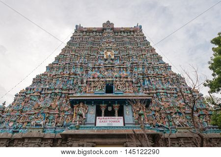 Madurai India - October 19 2013: Vertical shot along the facade of the East Gopuram. End in the sky. Abundance of statues and pallet of pastel colors.