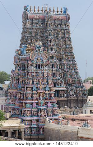 Madurai India - October 19 2013: Closeup of the South Gopuram of the Meenakshi Temple against faint blue sky. Partly hidden by the Vimanam of the temple proper.