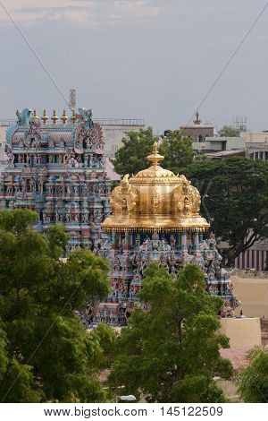 Madurai India - October 19 2013: The golden dome of the Meenakshi shrine on the temple grounds sits on top of short Vimanam. Other Vimanam in photo too.