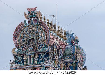 Madurai India - October 19 2013: Closeup of the East Gopuram of the Meenakshi temple. Plenty of pastel colors and statues.