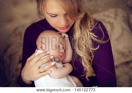 Young beautiful mother holding sleeping newborn baby on hands in the bedroom. The woman lulls son pressed against his chest. Happy family at home.