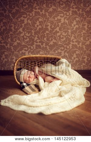 A newborn baby sleeps in a cozy room in a basket covered with a white knitted blanket. Little boy in hat fell asleep on the floor in an elegant interior. Family happiness