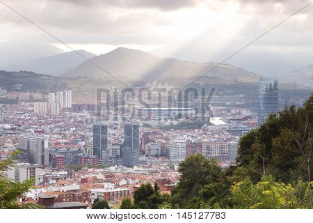 Bilbao Spain - September 1 2016: Sun rays touching the city of Bilbao. View of the downtown from a near hillside. We can see the Isozaki gate San Mames football stadium or the Iberdrola tower.