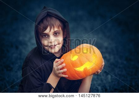 Child in scary costume holding a carved pumpkin. Child in halloween outfit at night with a jack-o-lantern.