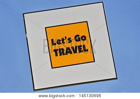 Text Lets Go Travel written on yellow road sign