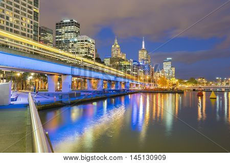 Melbourne, Australia - September 18, 2015: Multiple exposure image of skyscrapers and light trail of trains in downtown Melbourne, Australia at twilight.