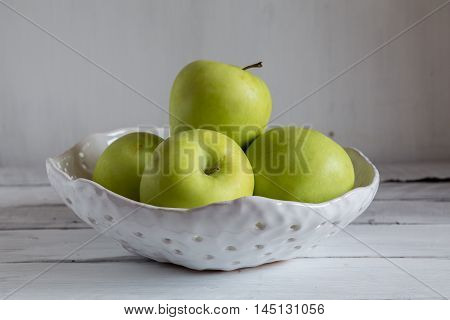 white ceramic colander with apples green apples in a clay colander green apples on white background.