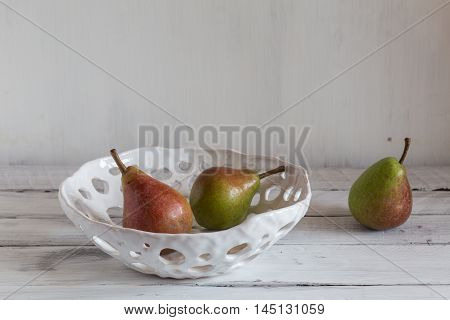 white ceramic colander with pears pears in a clay colander pears on white background