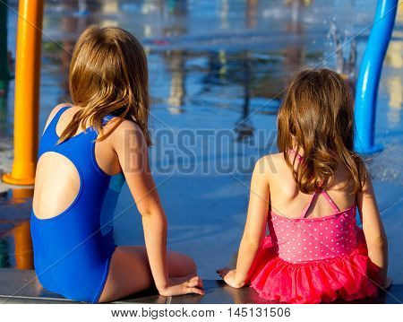 View of the backs of two young sisters in swim suits as they sit and look at a splash pad. The late afternoon sun is shining on them. There is copy space.