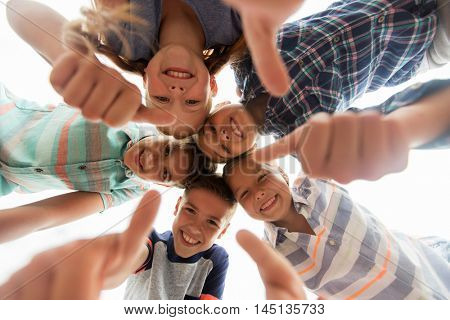 childhood, leisure, friendship and people concept - group of smiling happy children showing thumbs up in circle