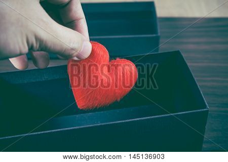 Human hand holding or putting a red heart-shaped in a black gift box for a Valentine's day concept of care and love colorized vintage picture style gift box is placed on a wooden table