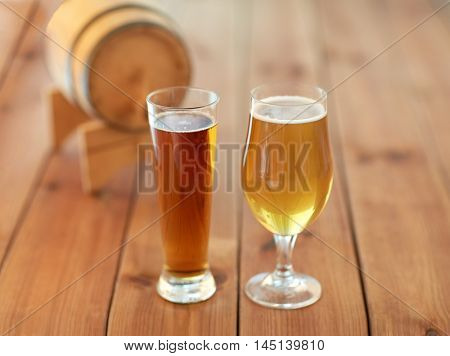 brewery, drinks and alcohol concept - close up of different beers in glasses and barrel on wooden table