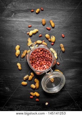Shelled peanuts in a jar. On the black wooden table.