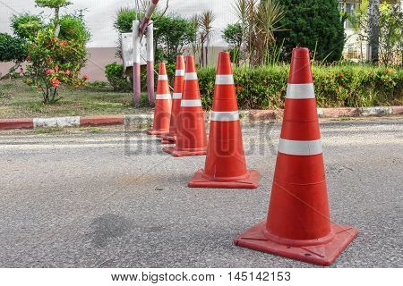 Traffic cone. Row  white and orange stripes on gray asphalt copy space.