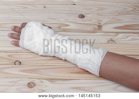 Gauze bandage the hand contusion. treating patients with  a wrist left male  wrapping his injury, On a wooden table poster
