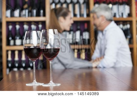 Red Wine In Glasses With Couple In Background