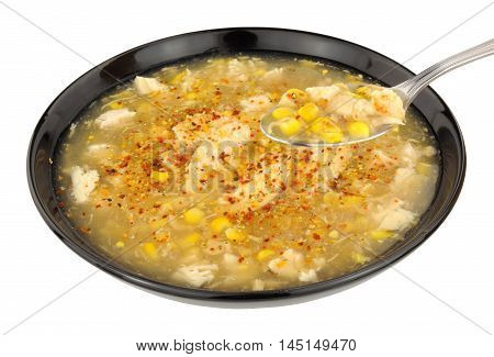 Chicken and sweetcorn soup in a black bowl isolated on a white background