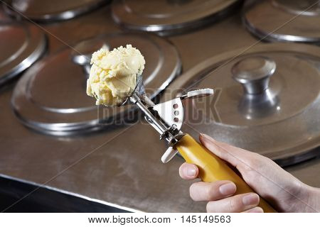 Waitress's Hand Holding Scoop With Vanilla Ice Cream At Shop