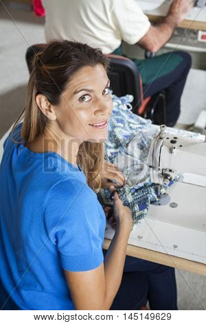Smiling Female Tailor Cutting Fabric At Workbench