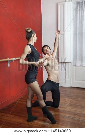 Trainer Kneeling While Performing With Ballerina