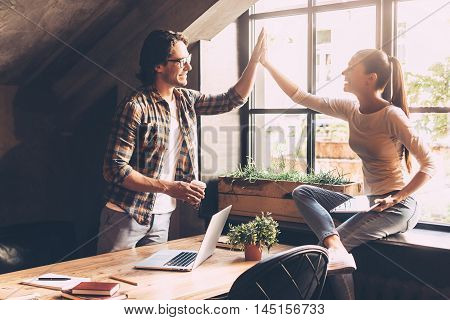 High-five! Cheerful young man and woman giving high-five while having coffee break in creative office