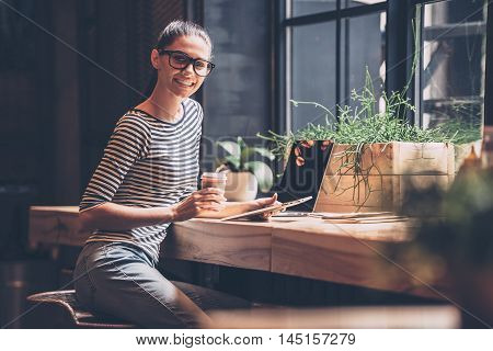 Having opportunity to work anywhere. Cheerful young woman holding digital tablet and coffee cup while sitting at the wooden counter in cafe