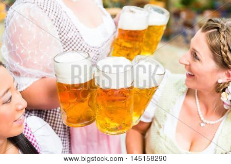 Close-up of waitress in Bavarian clothes serving beer in five beer glasses to two women