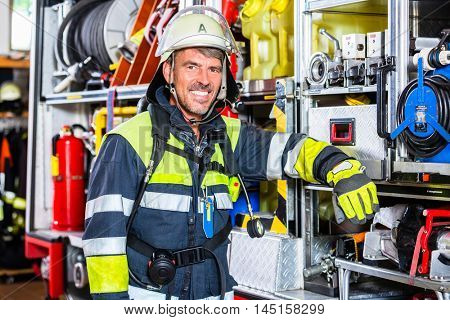 Fire fighter in uniform leaning at vehicle of fire department