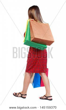 back view of going woman with shopping bags . girl in red plaid dress is thrown sideways back shopping bags.