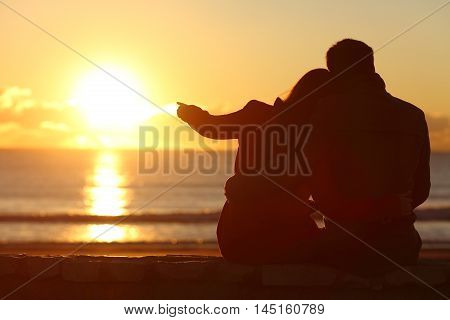 Rear view of a couple silhouette sitting cuddling and enjoying pointing at sun at sunset outside on the beach in winter