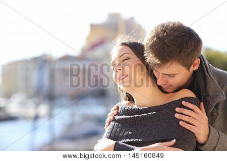 Affectionate and passionate elegant couple seducing and flirting with passion with a coast urban background in winter