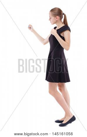 skinny woman funny fights waving his arms and legs. Blonde in a short black dress in a boxing rack.