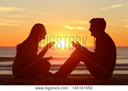 Side view of a full body of two friends or couple silhouette of teens sitting and talking at sunrise on the beach with the sun in the middle