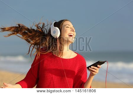 Happy girl wearing red colorful jersey dancing singing and listening music on line with headphones from a smart phone on the beach