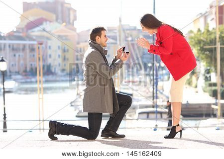 Profile of a proposal of a full body of a fashion elegant couple with a man asking marry to his girlfriend in an idyllic port of an urbanization