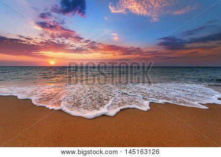 Colorful ocean beach sunrise. Golden sands and blue sky