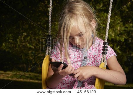 Beautiful Caucasian blond girl sitting on swing watching and playing on smart phone.