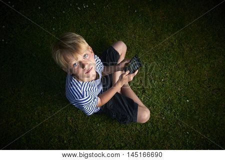 Child young boy with mobile phone outdoor. Child looking at the screen, playing, using apps. Boy playing with smartphone.