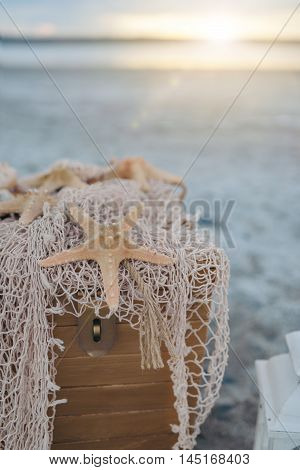 on the beach wooden box with network and starfish