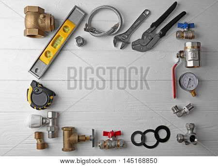 Plumber tools frame on white wooden background