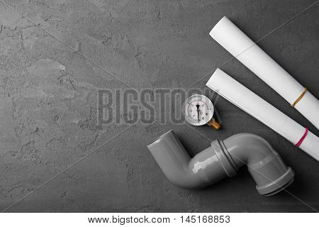 Plumber tools with blueprints on concrete structure background