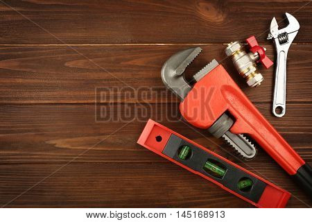 Plumber tools on a wooden background