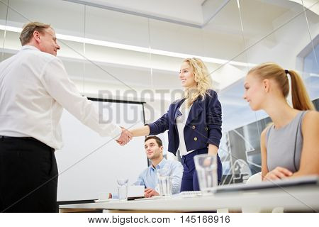 Manager gratulates succesful businesswoman in a business meeting