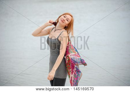 Outdoor portrait of a beautiful redhead woman on the sea