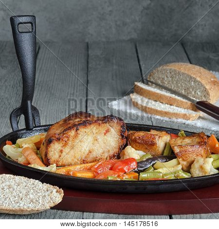 Fried pork with vegetables in a cast iron skillet and a wooden stand. Blue gray wood background, rustic style.