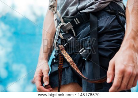 Close-up of rock climber wearing safety harness and climbing equipment outdoors