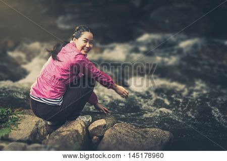 Vacation lifestyle scene of woman wearing sport cloths sitting beside canal in morning time. Woman activity on holiday concept with vintage filter effect
