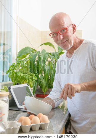a senior man cooking in the kitchen at home